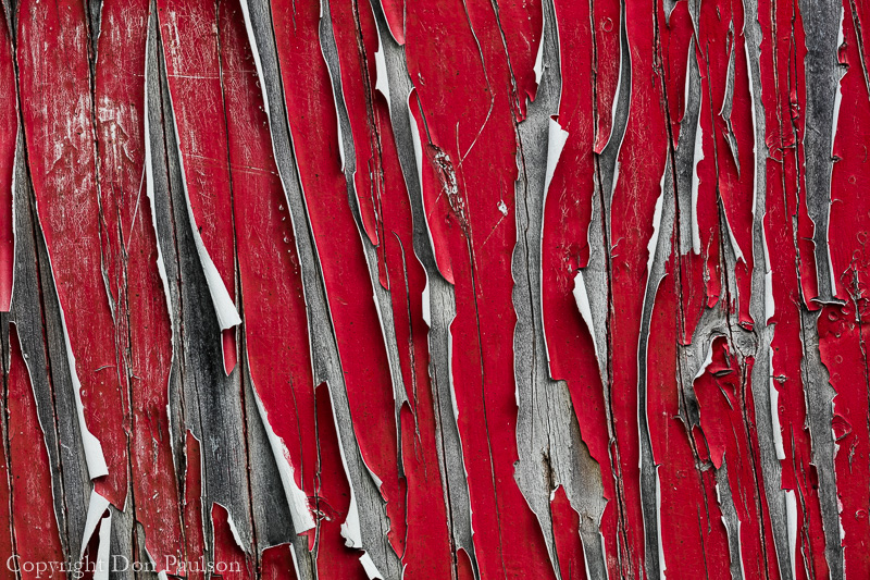 Peeling red paint on wood