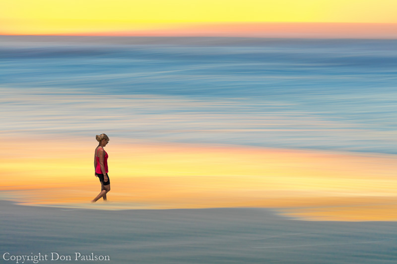 Composite image of a woman wading in the surf and an abstract motion blur of sunset and ocean Surf - Washington, Cape Disappointment State Park