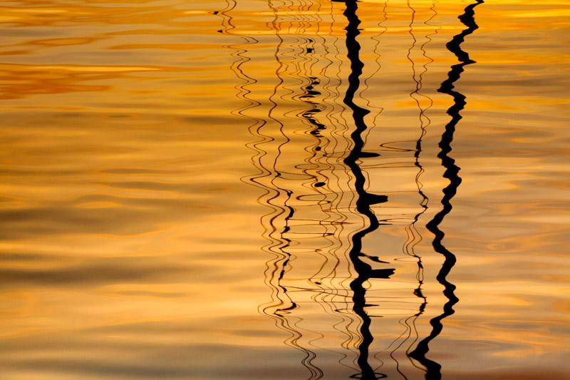 Sailboat mast reflection at sunset, San Juan Islands,