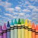 Crayons forming a rainbow with sky in background